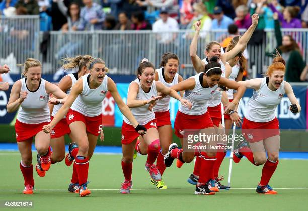 The England players celebrate as goal keeper Maddie Hinch saves the deciding penalty shuttle to put England through to the Gold Medal final during...
