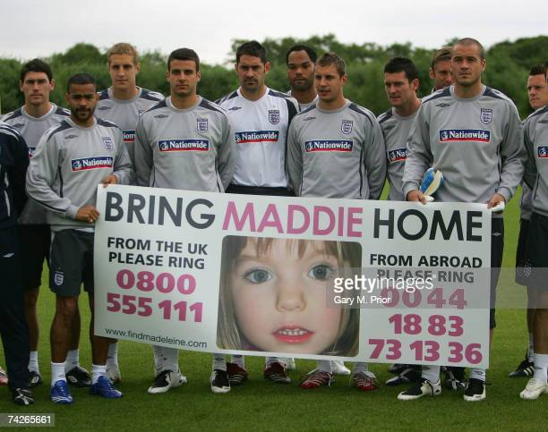 The England players hold a banner for the safe return of missing child Maddie McCann before England B team training at the Carrington training ground...