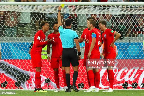 The England players protest to Referee Wilmar Roldan after he awarded a penalty to Tunisia and shows Kyle Walker of England a yellow card during the...
