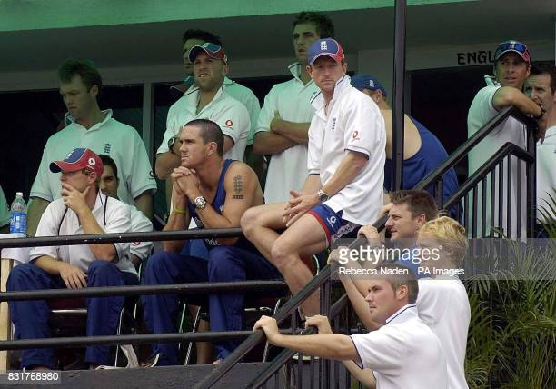 The England players watch as fires are started in the stands by cricket fans after the 5th ODI between England and India was abandoned at the Nehru...