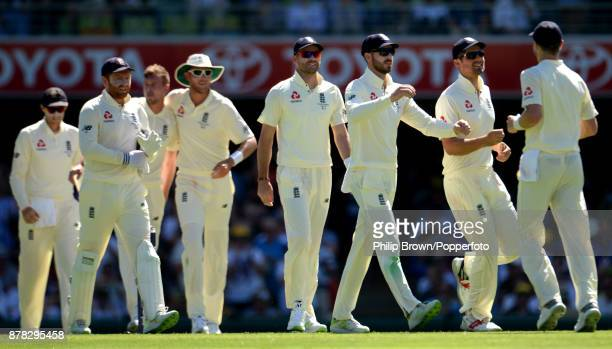 The England team celebrate after the dismissal of David Warner of Australia on the second day of the first Ashes cricket test match between Australia...