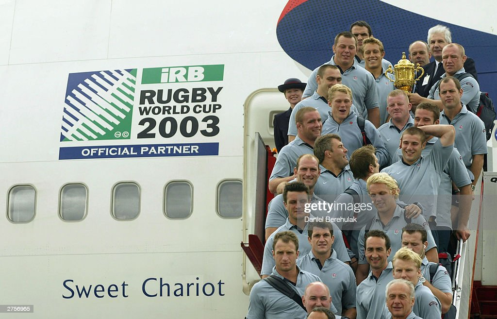 The England team hold aloft the Webb Ellis Trophy on the stairs of the British Airways BA16 aircraft during the departure of the England Rugby team at Sydney International Airport November 24, 2003 in Sydney, Australia. (Photo by Daniel Berehulak/Getty Images) The England Rugby Team depart Sydney victorious after winning the Rugby World Cup defeating Australia 20:17 in the final.