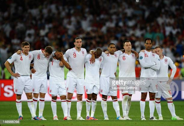 The England Team look on in despair as Ashley Cole walks up to take his penalty during the UEFA EURO 2012 quarter final match between England and...