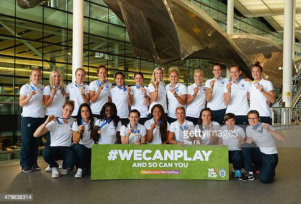 The England team pose for the camera as the England Women's Team arrive back from the World Cup at Heathrow Airport on July 6, 2015 in London,...