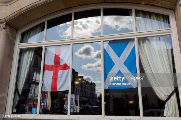 The English Cross of St. George and the Scottish Saltire flags hang together in a pub window, on 2nd October 2019, in Sutton, London, England. Voters...