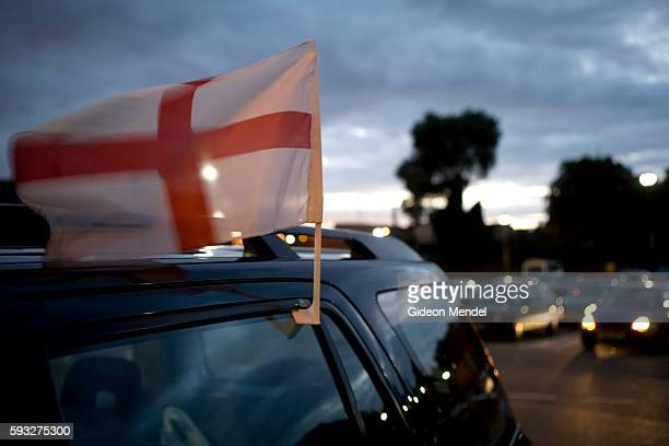 The English flag attached to a car parked in at a supermarket in Hackney in London flaps in the wind This flag displaying the Cross of St George used...