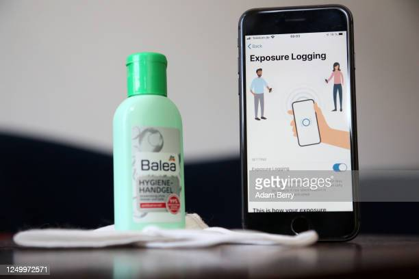 The English version of the German federal health ministry's Corona-Warn-App software is seen on an Apple iPhone next to a medical facial mask and a...