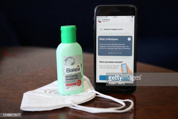 The English version of the German federal health ministry's CoronaWarnApp software is seen on an Apple iPhone next to a medical facial mask and a...