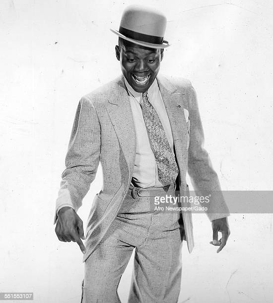 The entertainer dancer Bojangles in a suit and hat tap dancing and using a hand to point at his feet illustrating the move 1930
