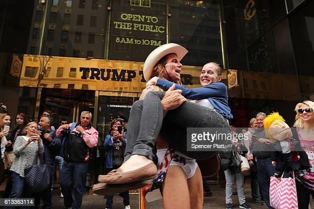 The entertainer Naked Cowboy carries a fan in front of Trump Tower in Manhattan on October 8 2016 in New York City The Donald Trump campaign has...