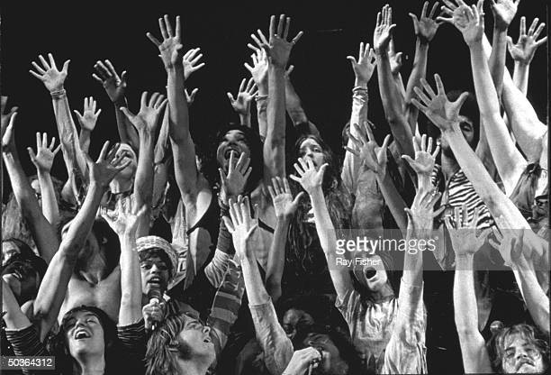 The entire cast of the stage musical Hair with their arms in the air.