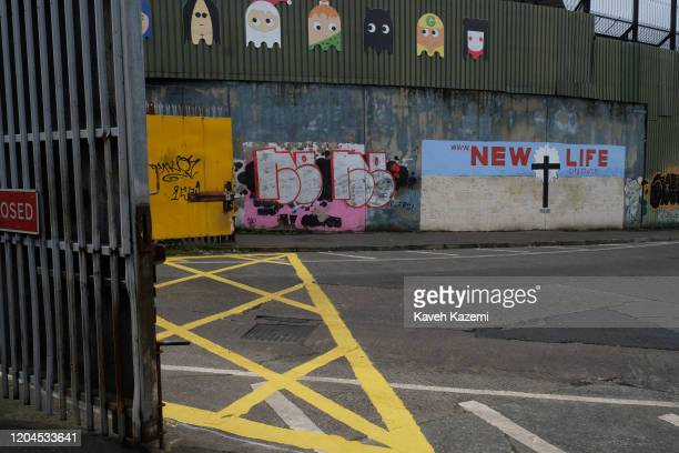 The entrance of the Cupar Way with a mural showing a Cross with written words promising a u201cNEW LIFEu201d painted under the high wall and fences...