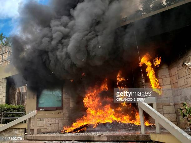 The entrance of the US embassy in Tegucigalpa burns after being set on fire by demonstrators of the education and health sectors protesting against...