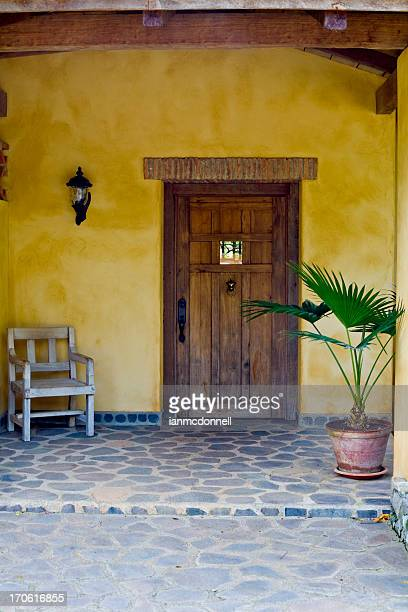 the entrance to a yellow house with a dark wooden door - guanacaste stock pictures, royalty-free photos & images