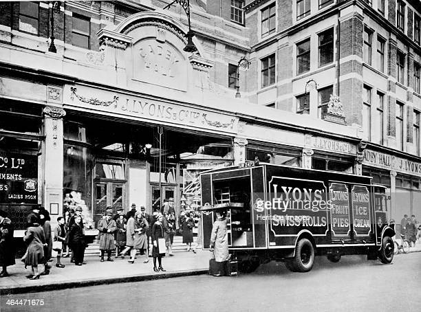 The entrance to Cadby Hall West Kensington London Parked outside is a Lyons van the side of which advertises their swiss rolls fruit pies and ice...