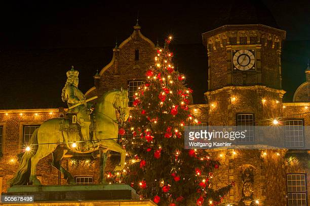 The equestrian statue of Jan Wellem illuminated at night and Christmas decorations in front of the old town hall in the old town of Dusseldorf,...