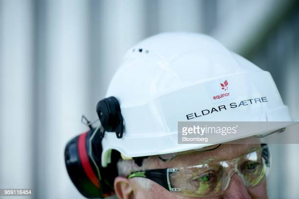 The Equinor ASA logo sits on the hard hat of Eldar Saetre chief executive officer of Equinor ASA on board the Troll A natural gas platform operated...