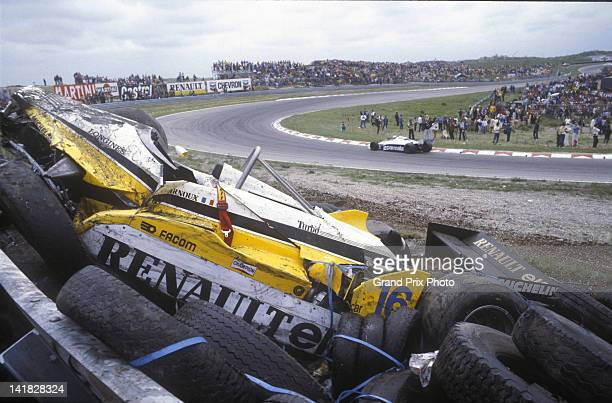 The Equipe Renault Elf Renault RE30B Renault V6 turbo driven by Rene Arnoux of France lays atop the tyre barrier after crashing out of the Dutch...