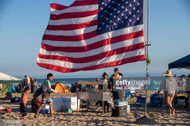 The Espinoza, Vazquez and Romero families of Fallbrook grill tacos on the beach beneath their giant American flag as they await the fireworks over...