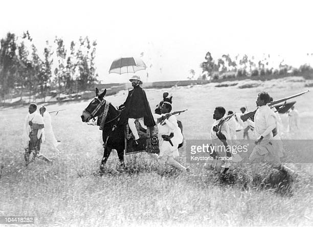 The Ethiopian emperor and dictator Halie SELASSIE wearing a colonial helmet and carrying a parasol leading his troops to the northern front of...