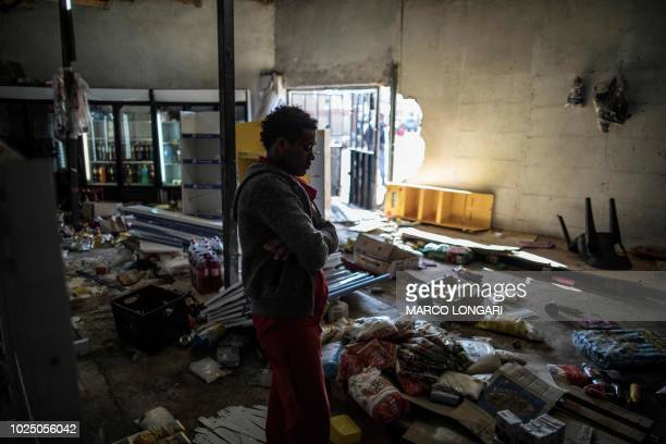 The Ethiopian owner of a looted grocery store in Soweto Johannesburg stands in his ransacked shop on August 29 2018 during unrest that erupted after...