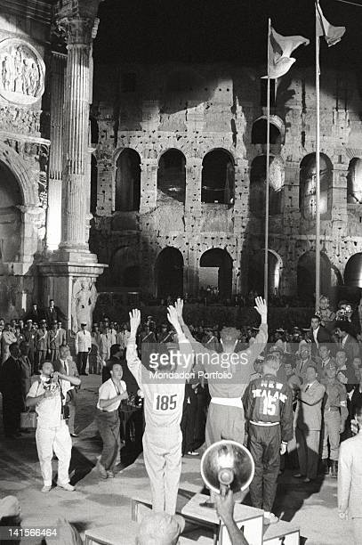 The Ethiopian runner Abebe Bikila raising his arms to the sky during the marathon prize giving ceremony at Rome Olympics. Rome, September 1960