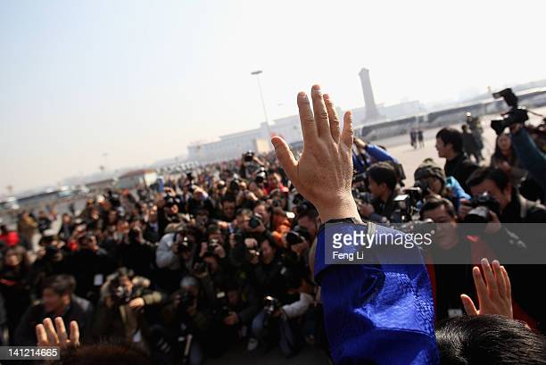The ethnic minority delegates wave to photographers as they leave the closing ceremony of the Chinese People's Political Consultative Conference at...