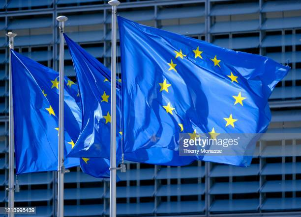 The EU flags are seen in front of the Berlaymont the EU Commission headquarter on May 19 in Brussels Belgium The authorship of the flag is due to a...