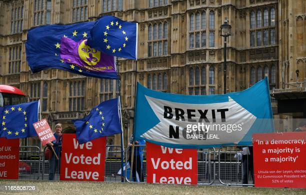 TOPSHOT The EU flags of antiBrexit activists fly as proBrexit activists stand with their placards and demonstrate near the Houses of Parliament in...