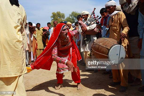 The eunuch performing dance with the beat of drums and bag pipes at the village festival of Multan during a Ox race day. The villagers enjoying and...