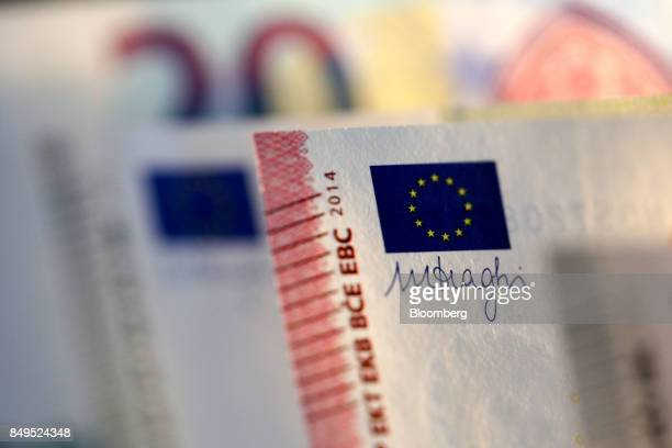 The Euro flag and the signature of Mario Draghi governor of the European central bank are displayed on the corner of a ten euro banknote in this...