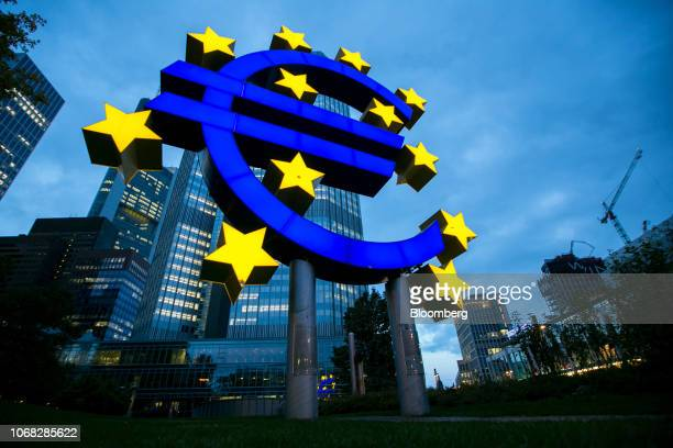 The euro sign sculpture stands illuminated outside the former European Central Bank headquarters at dusk in Frankfurt Germany on Thursday Oct 20 2016...