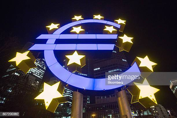 The euro sign sculpture stands illuminated outside the former European Central Bank headquarters at night in Frankfurt Germany on Wednesday Jan 27...
