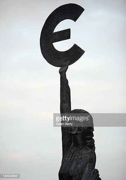 The 'Europe' sculpture by Belgian artist May Claerhout showing a woman holding up the symbol of the Euro stands outside the European Parliament...