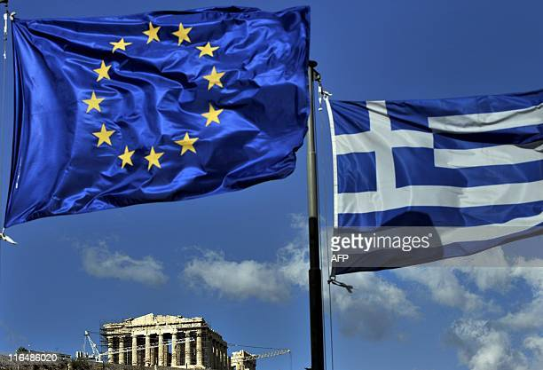 The European and the Greek flags fly above the ancient temple of Parthenon atop the Acropolis hill in Athens on May 10 2011 Experts from the European...