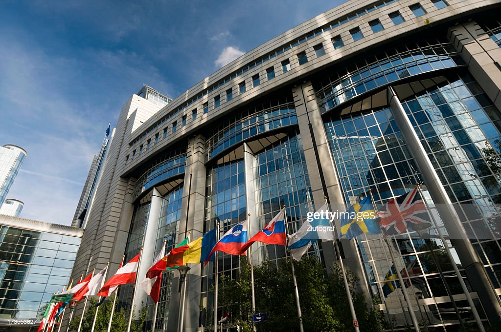 The European Parliament in Brussels with flags outside : Stock Photo