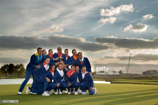 The European Team celebrate with the trophy after securing victory in the singles matches of the 2018 Ryder Cup at Le Golf National on September 30,...