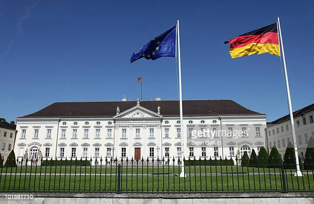 The European Union and German flags sway over Schloss Bellevue which serves as the German presidential palace on June 3 2010 in Berlin Germany German...