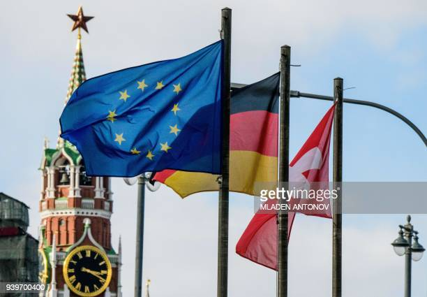 The European Union flag flies among others in front of the Kremlin's Spasskaya Tower in Moscow on March 29, 2018. At least 25 countries have ordered...