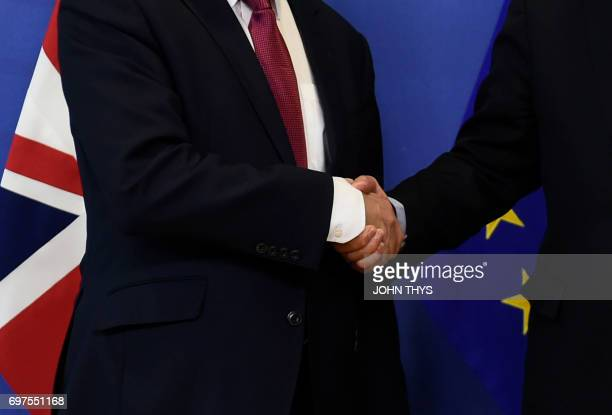 The European Union's chief negotiator Michel Barnier shakes hands with British Secretary of State for Exiting the European Union David Davis during a...