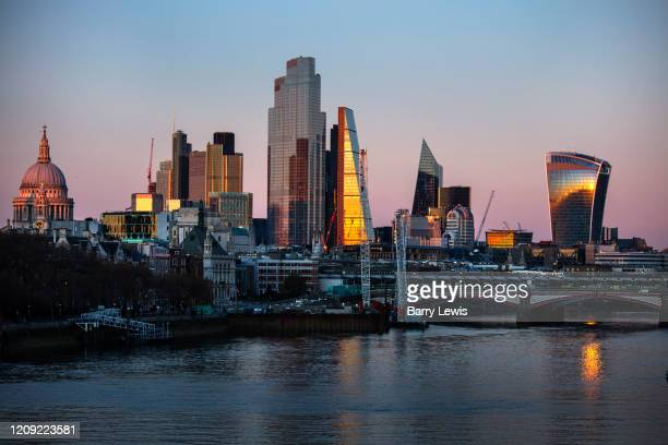 The evening light on the City of London skyline by the river Thames which was nearly deserted at 7pm during the Coronavirus pandemic on 4th April...