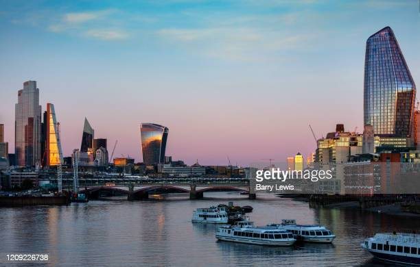 The evening light on the skyline of the building on the river Thames, which was nearly deserted at 7pm during the Coronavirus pandemic on 4th April...