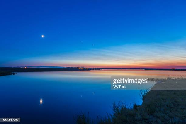The evening planets of Venus and Jupiter to the right of the waxing crescent Moon on the evening of summer sosltice June 21 2015 The star Regulus is...