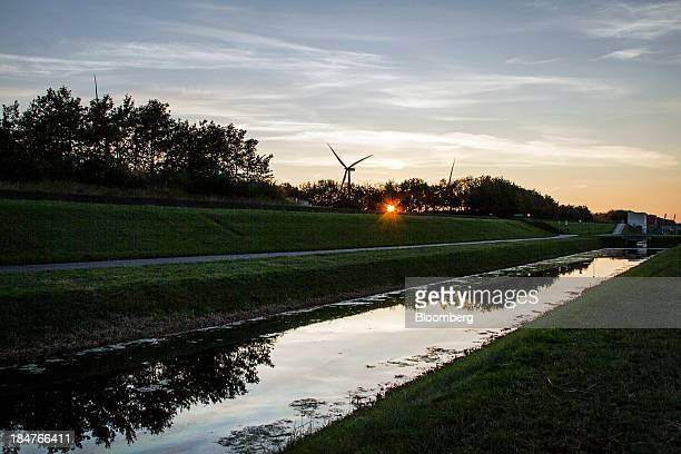 The evening sun is seen setting behind wind turbines operated by Dong Energy A/S at the company's power plant site in Hvidore Denmark on Monday Oct...