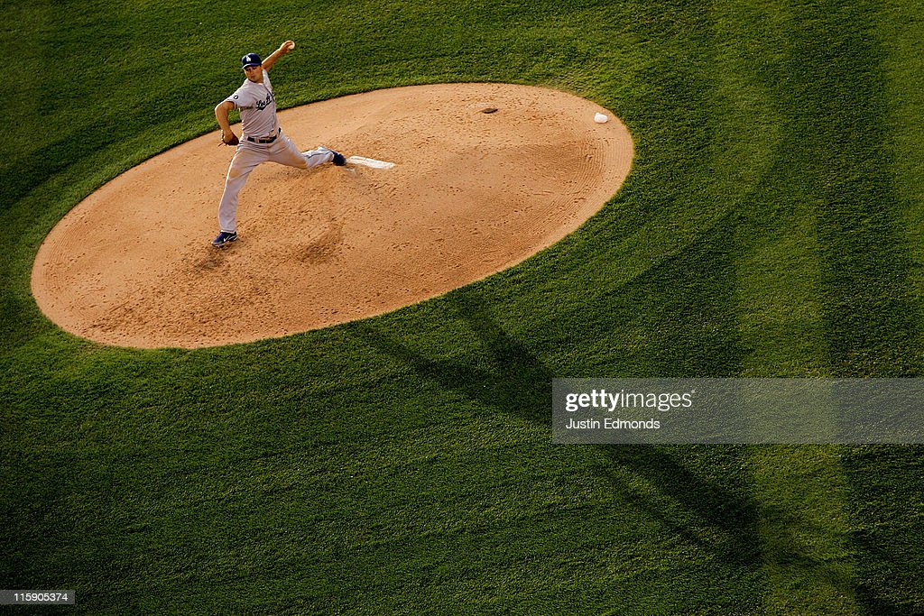 The evening sun sweeps across the mound as starting pitcher Ted Lilly #29 of the Los Angeles Dodgers works the fifth inning against the Colorado Rockies at Coors Field on June 11, 2011 in Denver, Colorado.