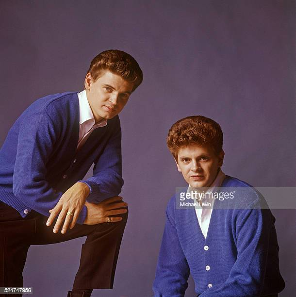 The Everly Brothers posing together in matching blue sweaters