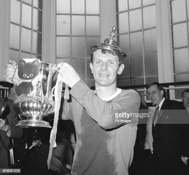 The Everton captain Brian Labone wears the top of the Football Association Cup on the top of his head as he proudly displays the cup and a lucky...