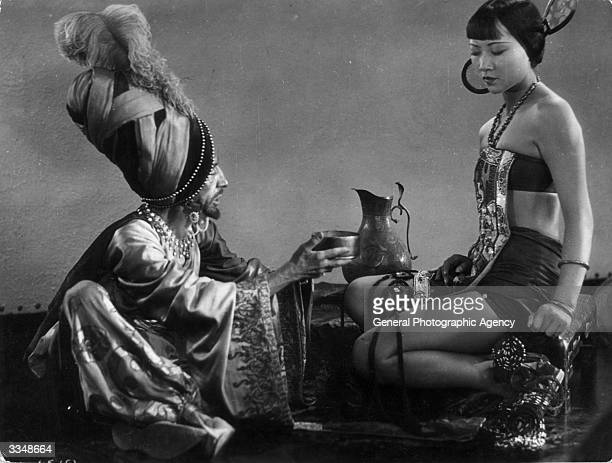 The evil associate played by Snitz Edwards discusses the Princess with Anna May Wong in 'The Theif Of Bagdad' a flamboyant silent film which borrows...