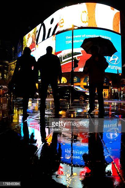 The exciting bright lights of London's West End and the famous Piccadilly Circus at night. Londoners and tourists enjoying the night life, are seen...