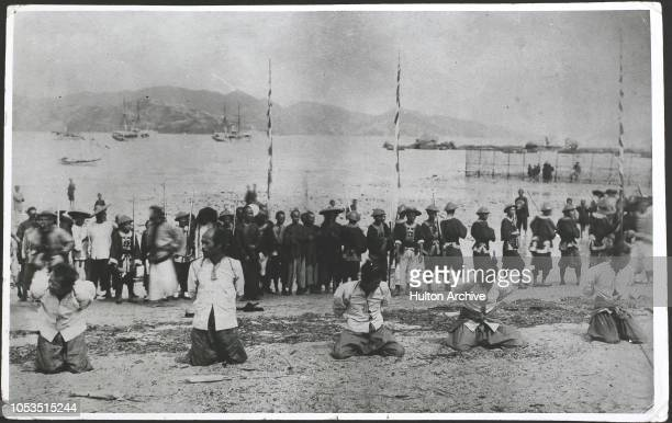 The execution of the Whampoa pirates by the British on the shore at Kowloon Hong Kong The condemned men kneel in line waiting for death